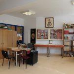 Szafy, biurka, krzesła oraz wiszące i stojące gabloty wystawiennicze