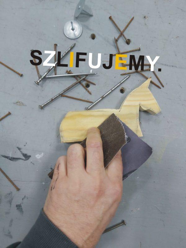Dłoń szlifująca papierem ściernym drewnianą figurkę konika