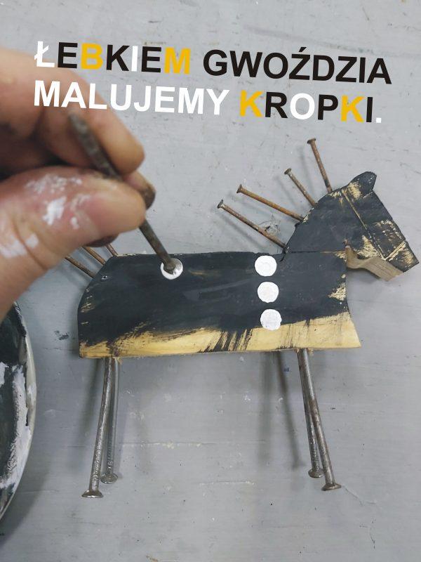 Dłoń malująca łebkiem gwoździa kropki na figurce