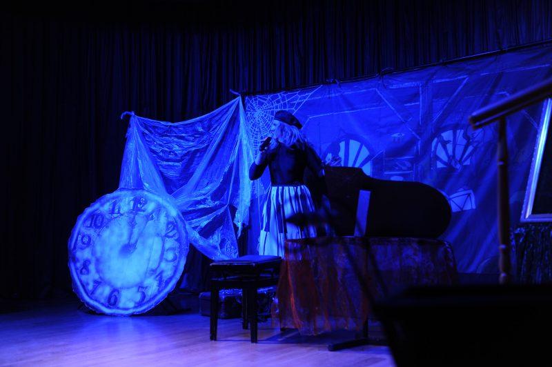 Aktorka na scenie, tarcza starego zegara, skrzydło fortepianu
