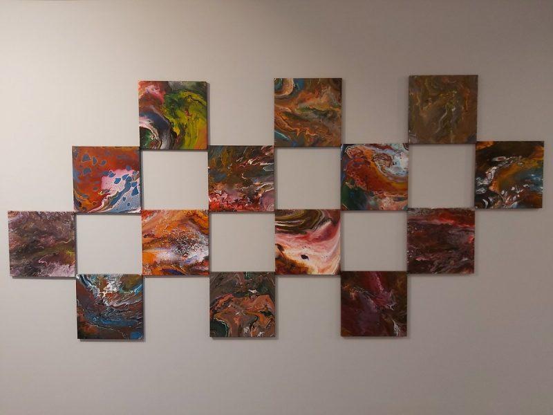 Kwadratowe obrazy na płótnie w technice pouringu zawieszone na ścianie w kompozycji szachownicy