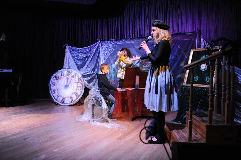 Chłopiec gra na fortepianie, aktor dyryguje, aktorka mówi do mikrofonu, tarcza starego zegara, balustrada