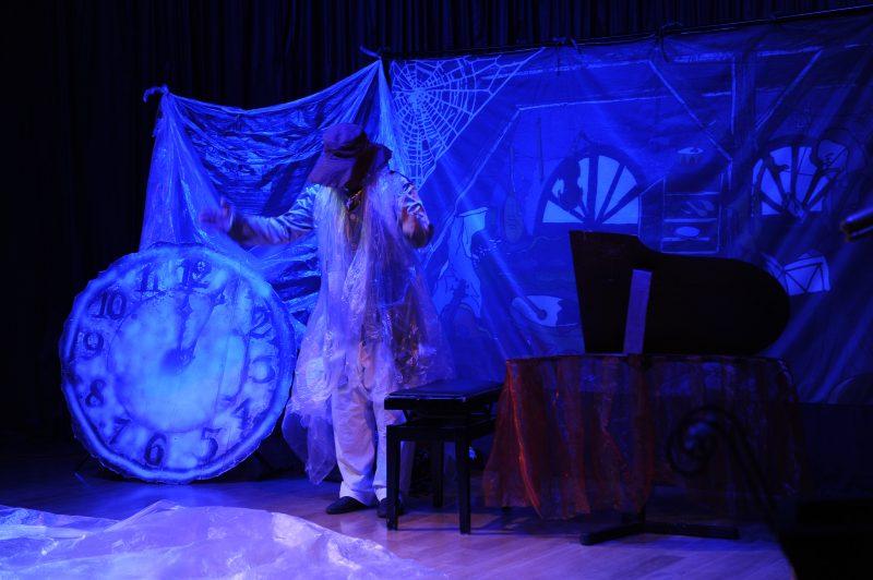 Aktor na scenie, tarcza starego zegara, skrzydło fortepianu
