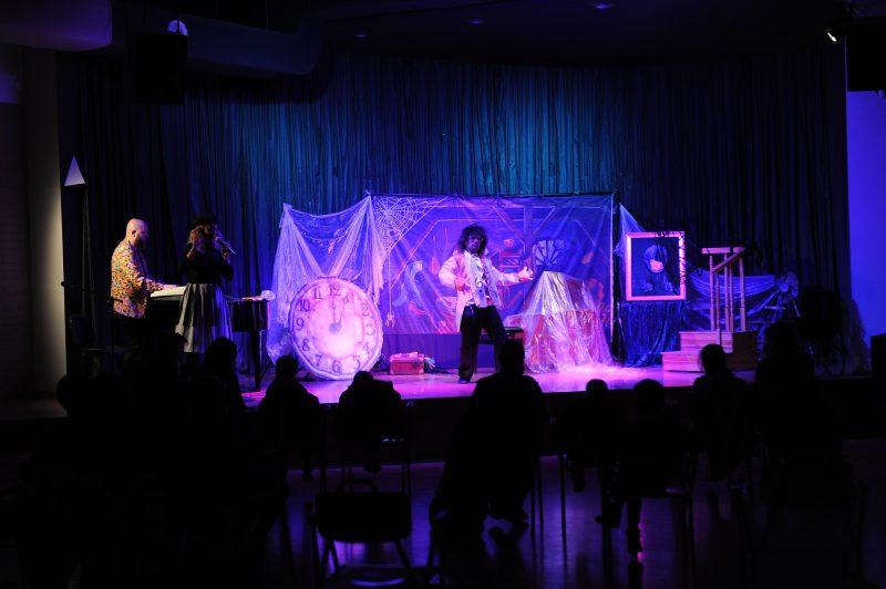 Pianista i aktor na scenie, ciemne sylwetki publiczności