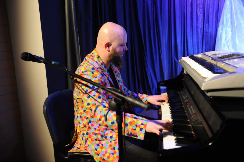 Pianista w marynarce w kolorowe kropki gra na fortepianie