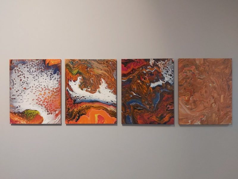 Cztery prostokątne obrazy w technice pouringu na ścianie