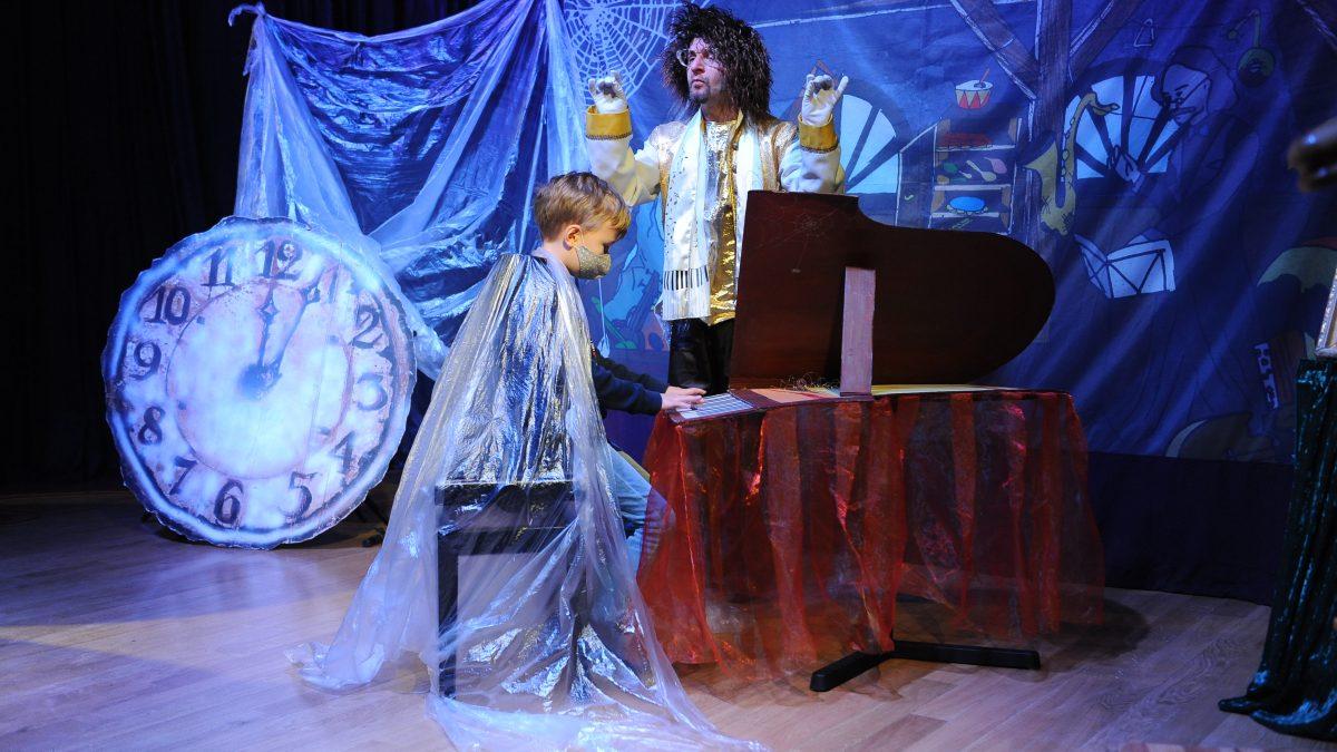 Chłopiec w pelerynie gra na fortepianie, aktor dyryguje, tarcza starego zegara