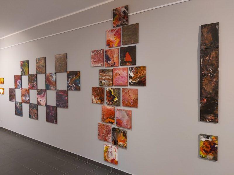 Ściana galerii z obrazami w kompozycji szachownicy, rozproszonych kwadratów i wykrzyknika