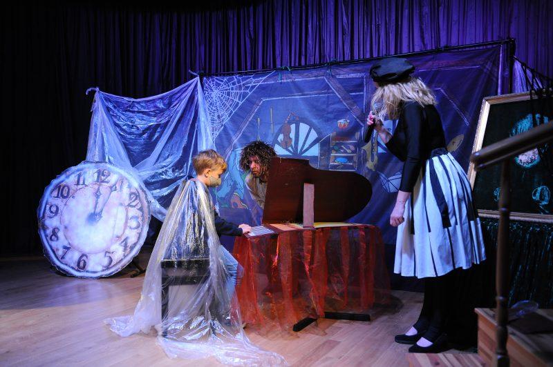 Chłopiec w pelerynie gra na fortepianie, aktor pochyla się do niego, aktorka mówi do mikrofonu, tarcza starego zegara