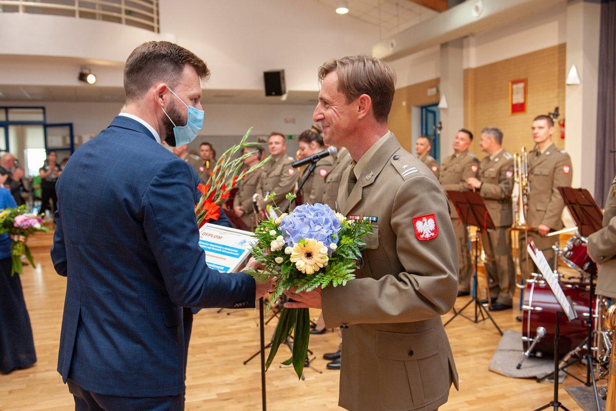 Mężczyzna w mundurze odbiera dyplom