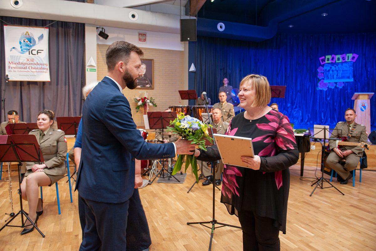 Zastępca burmistrza miasta wręcza kwiaty dyrygentce