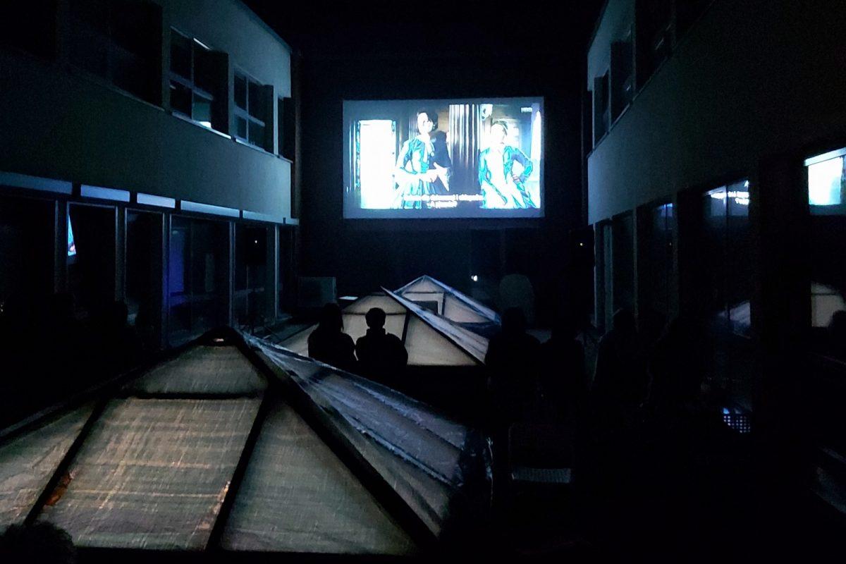 Rozświetlony w ciemności ekran kinowy i sylwetki widzów