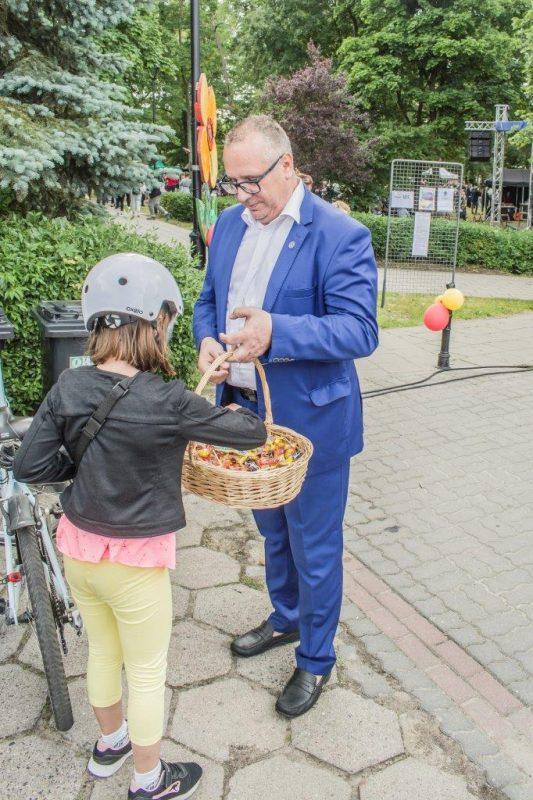 burmistrz częstuje cukierkami dziewczynkę