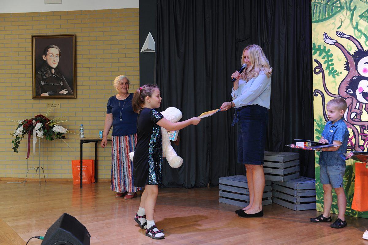 Dziewczynka odbiera nagrodę na scenie