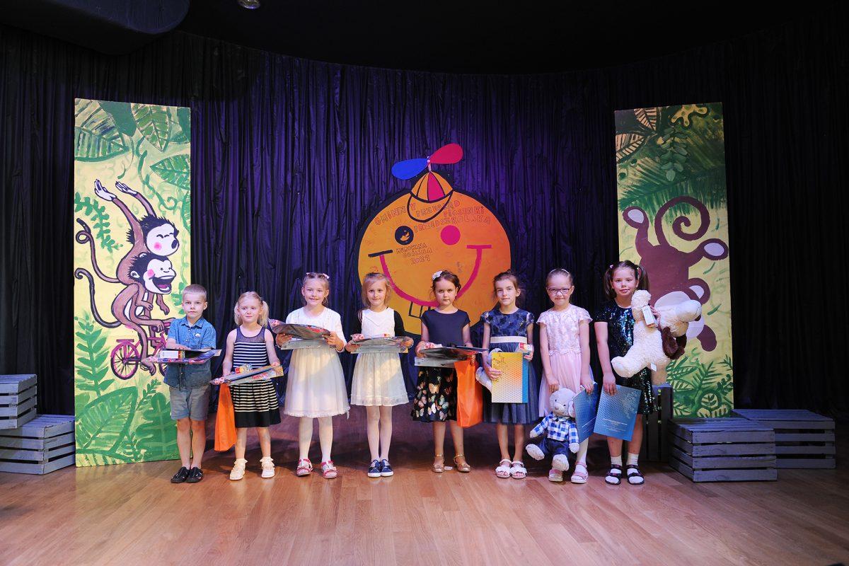 Grupa dzieci na scenie pozuje do pamiątkowego zdjęcia