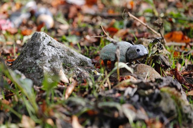 Figurka owada z gliny szkliwionej w naturalnym leśnym otoczeniu
