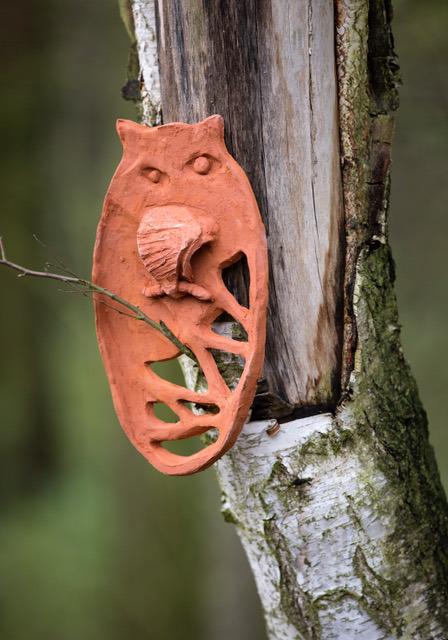 figurka sowy z wypalonej gliny w naturalnym leśnym otoczeniu