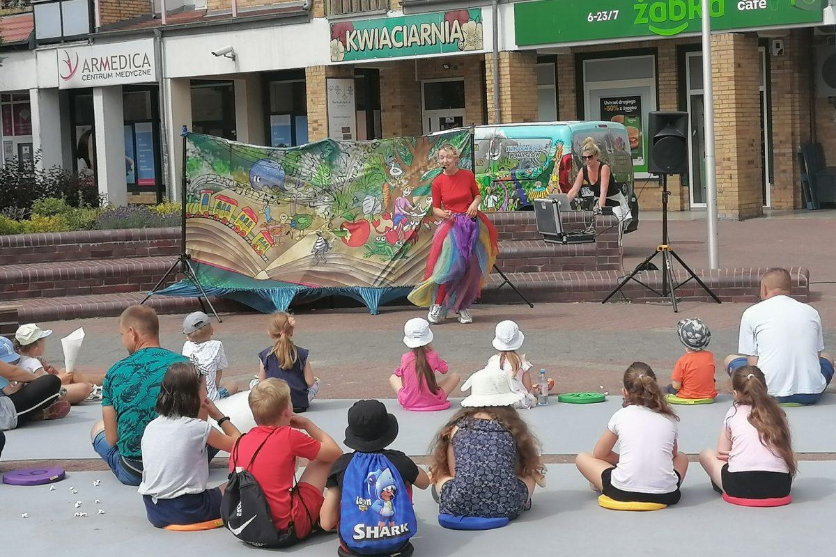 Dzieci siedzące przed występującą aktorką na placu