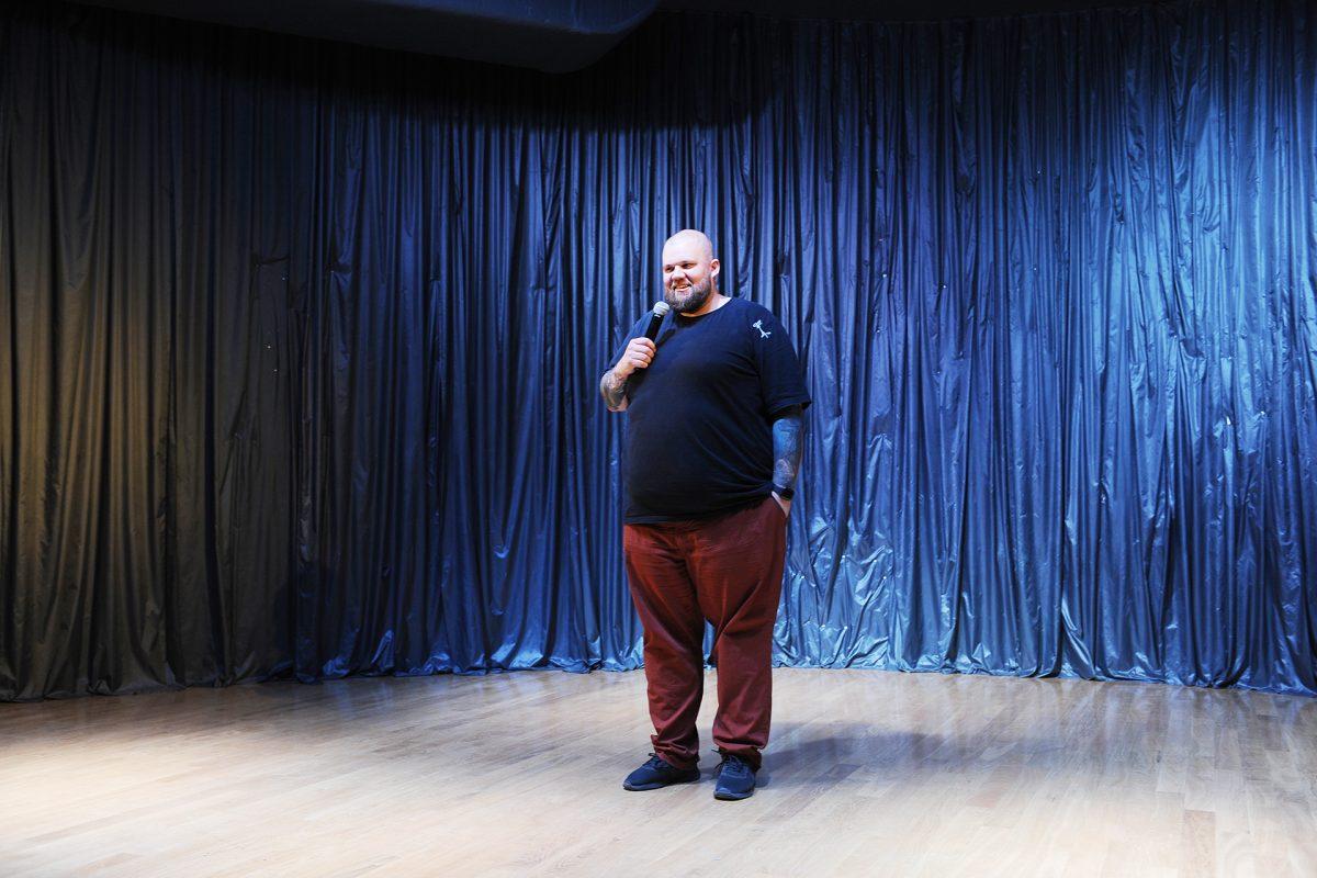 Mężczyzna z brodą, z ręką w kieszeni na scenie mówi do mikrofonu