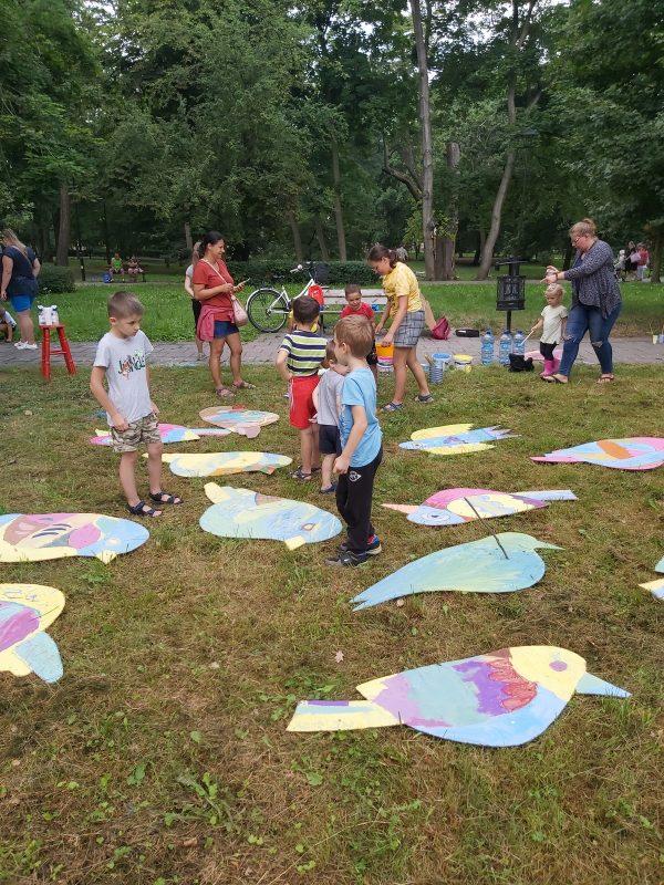 Grupa ludzi z dziećmi wśród leżących na trawie kolorowych ptaków wyciętych z płyty