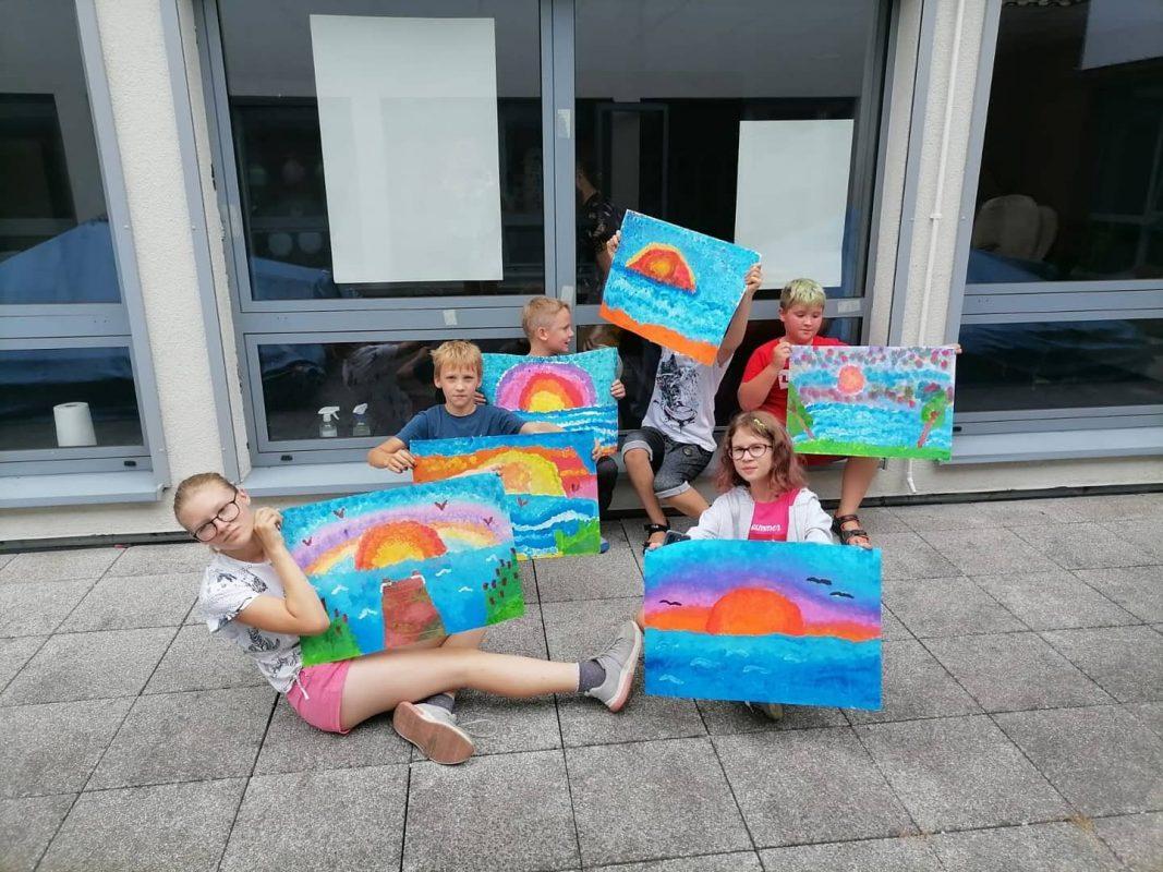 Dzieci pozują z wykonanymi pracami plastycznymi