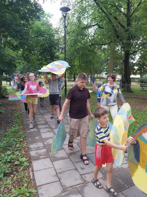 Przemarsz grupy dzieci z kolorowymi ptakami przez park