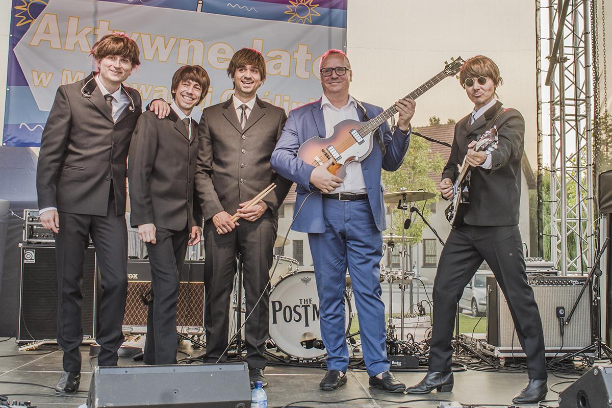 Burmistrz z gitarą pozuje z zespołem na scenie