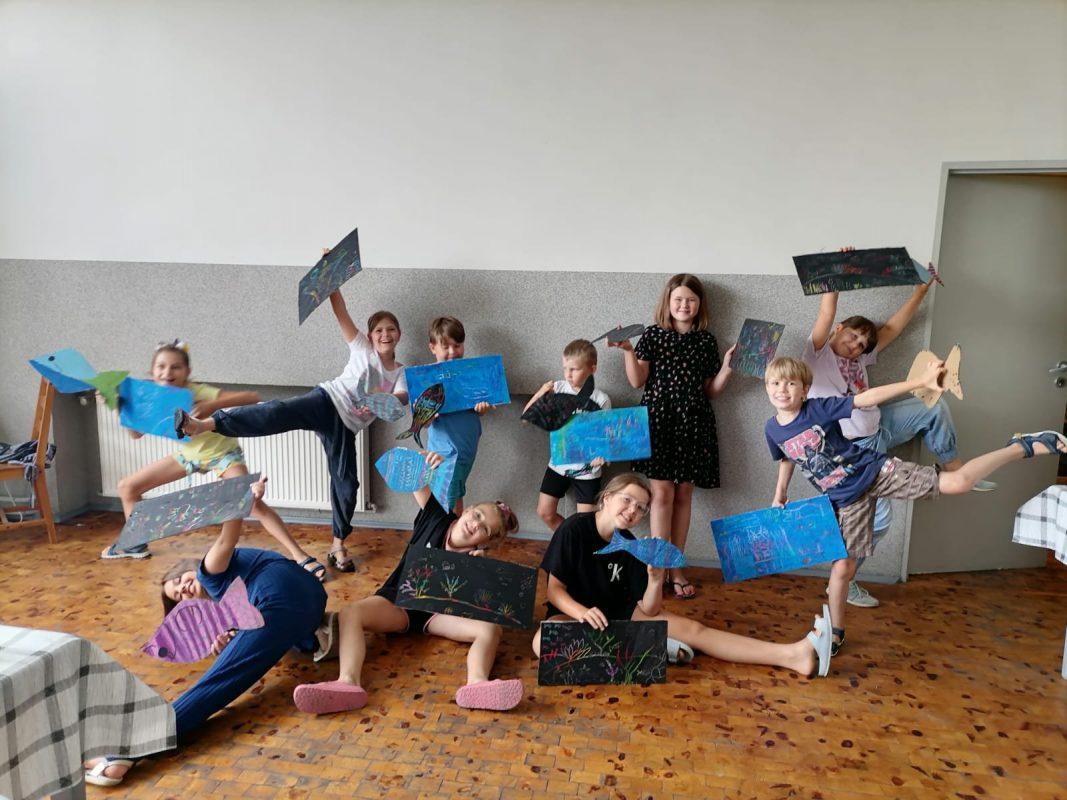 Dzieci z wykonanymi pracami plastycznymi w śmiesznych pozach
