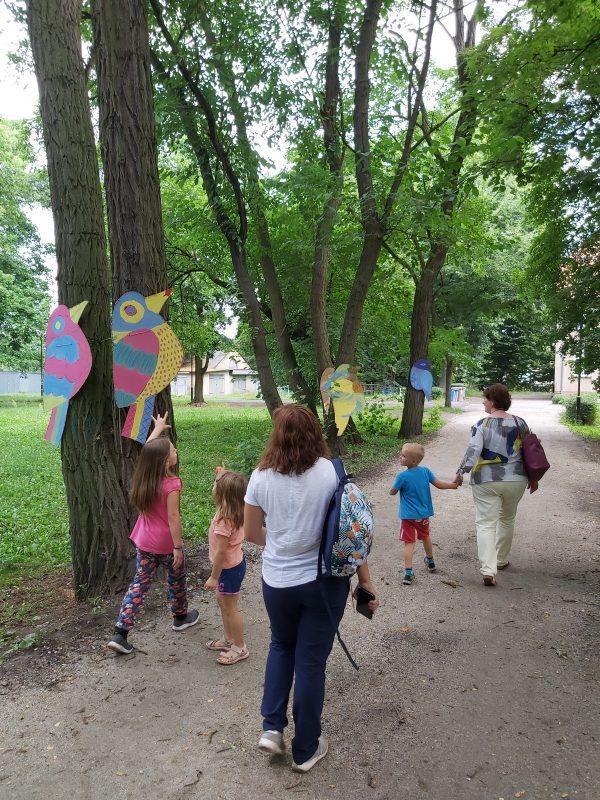 Ptaki na drzewach w parku, droga, ludzie idący drogą