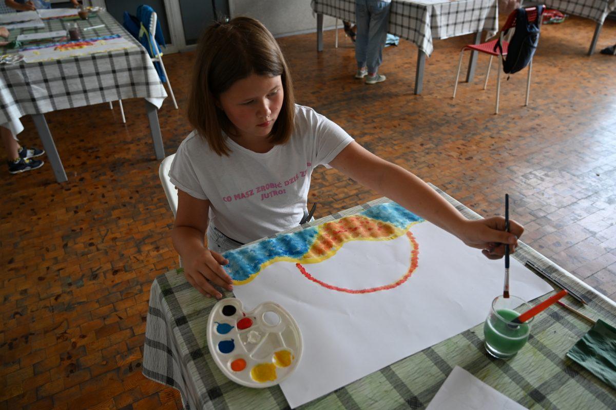 Dziewczynka maluje obrazek na papierze