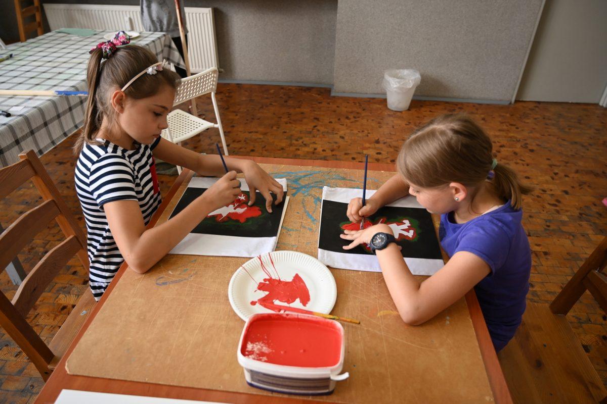 Dziewczynki malują za pomocą szablonu wzór na materiałowym worku
