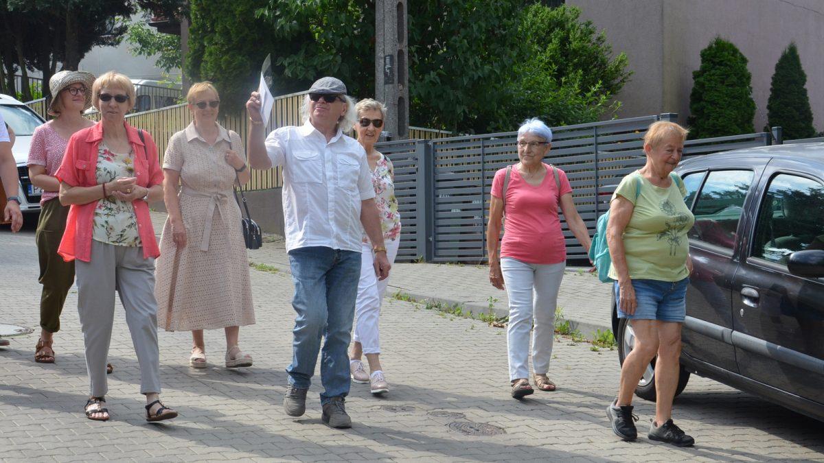 Grupa osób schodzi z górki po ulicy