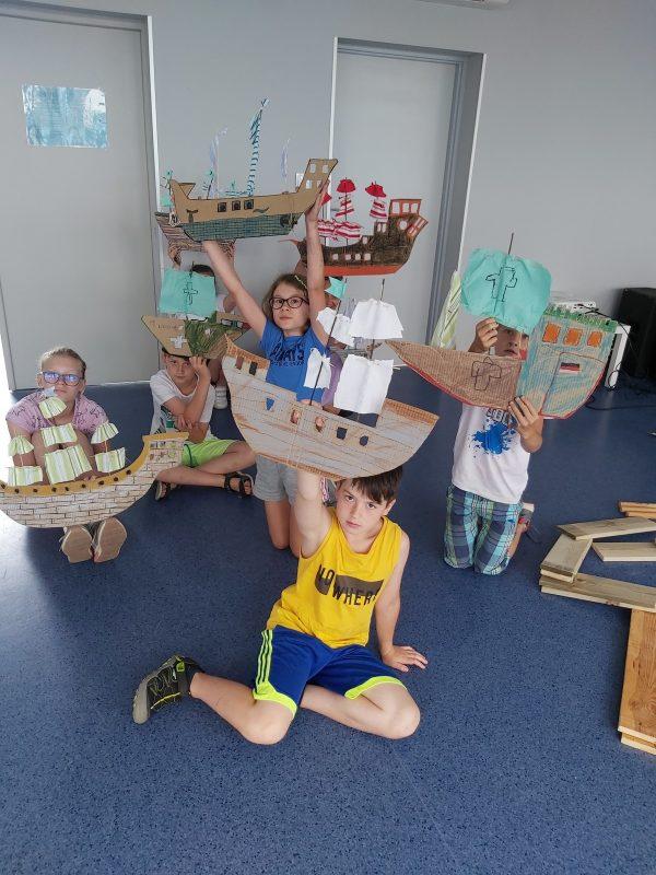 Dzieci pozują z wykonanymi okrętami z kartonu