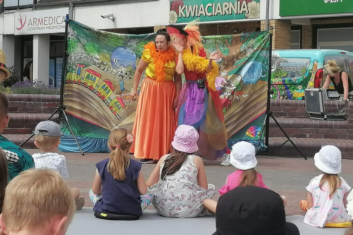 Dzieci siedzące przed występującymi aktorkami na placu