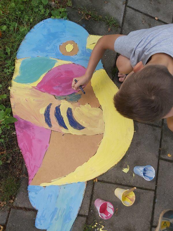 Chłopiec maluje na chodniku sylwetę wyciętego ptaka