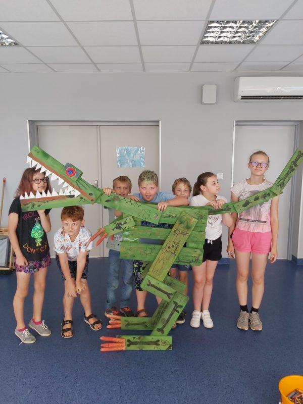 Dzieci pozują z wykonanym z palet i desek dinozaurem T.REX