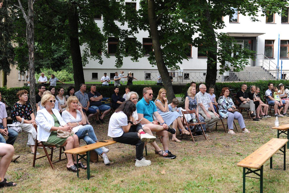 Publiczność na ławkach i krzesłach