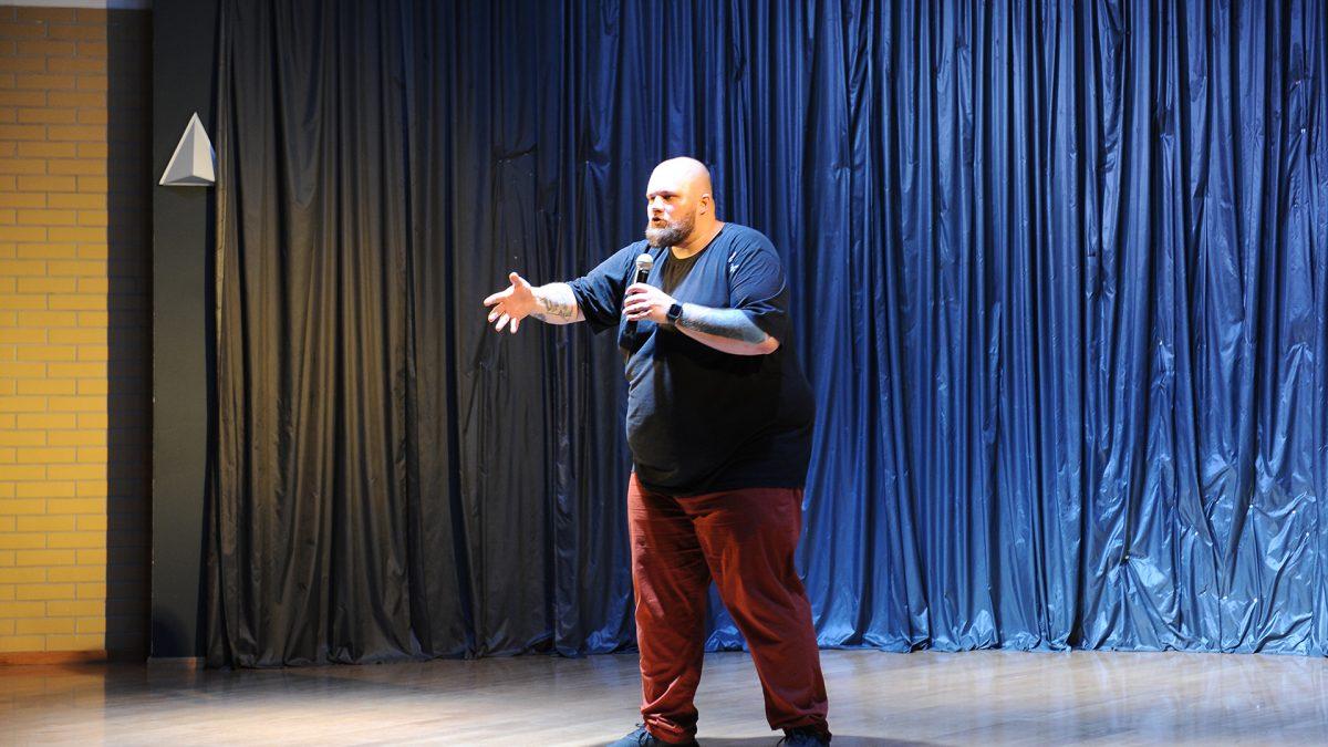 Mężczyzna z brodą na scenie gestykuluje ręką mówiąc do mikrofonu