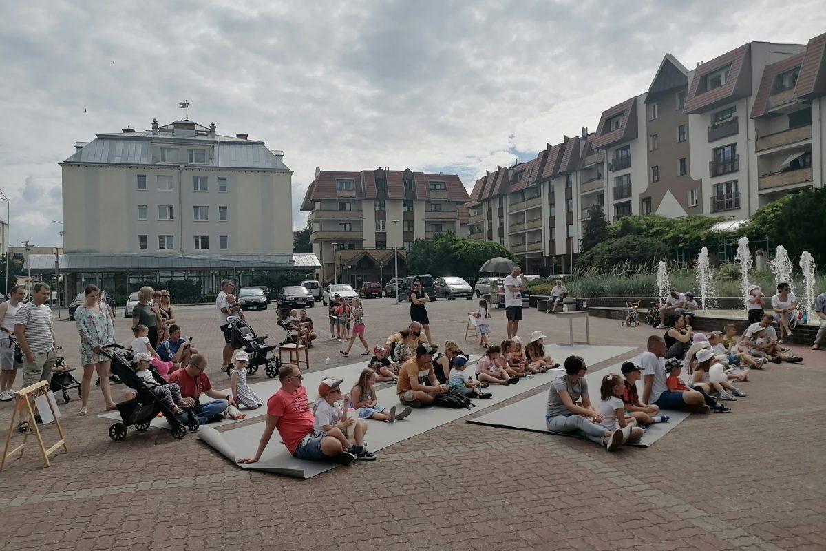 Publiczność siedząca na placu przy fontannie