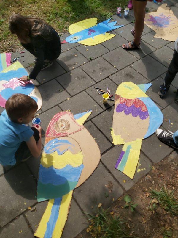 Dzieci malują ptaki na chodniku
