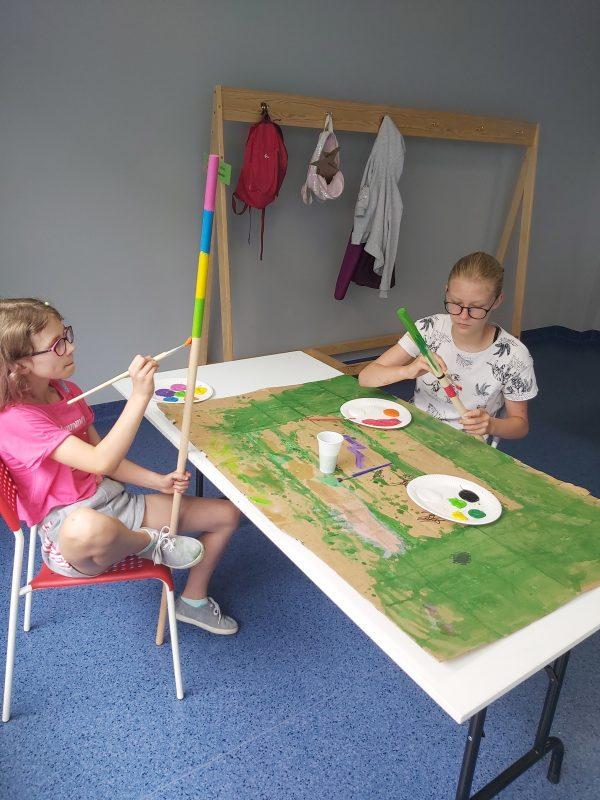 Dziewczynki przy stole malują kijki