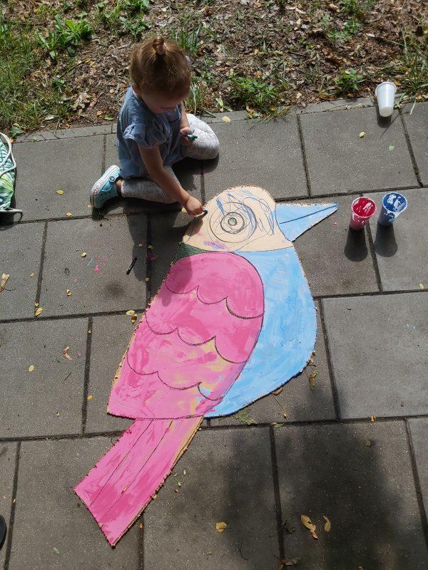 Dziewczynka maluje sylwetę wyciętego ptaka na chodniku