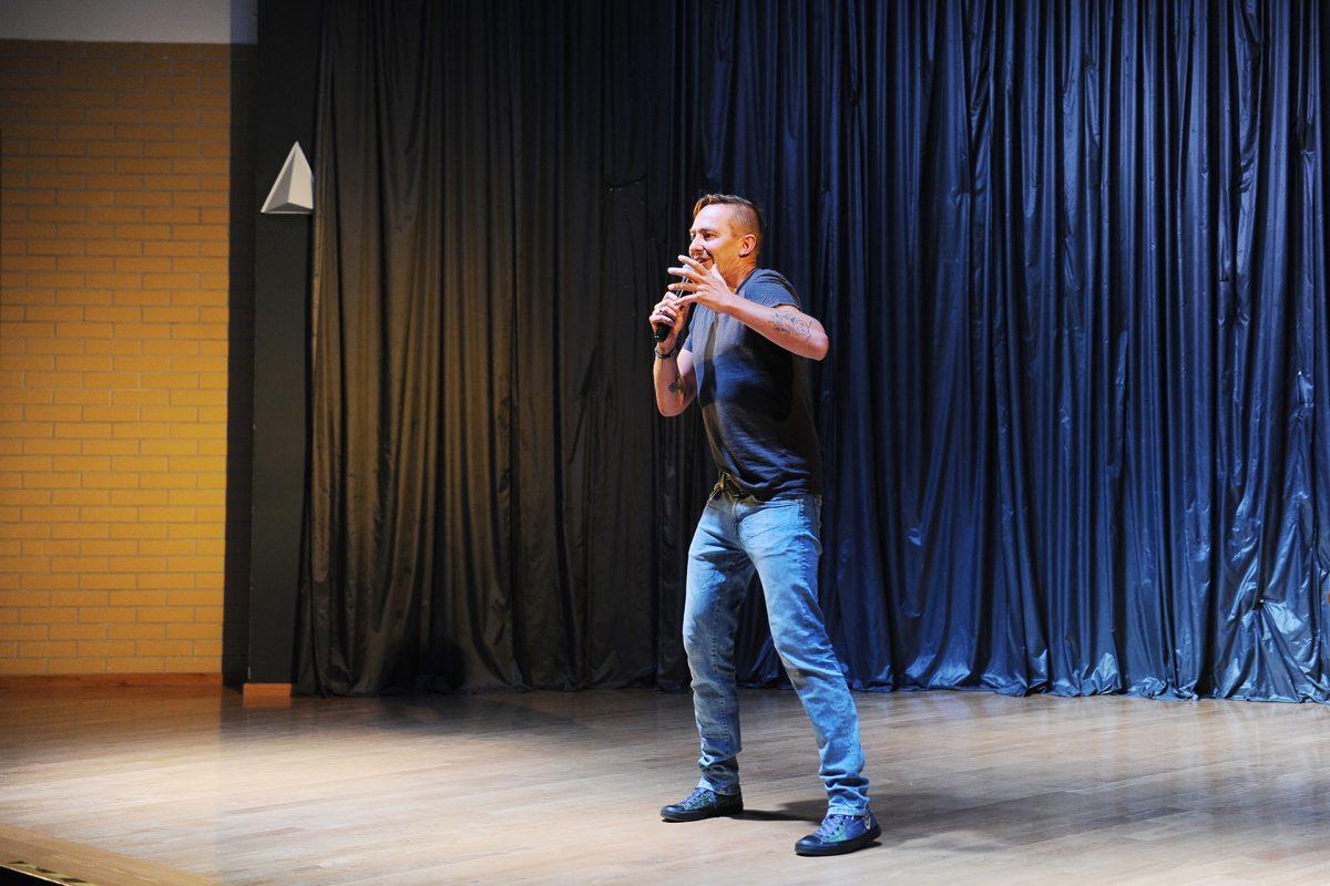 Mężczyzna na scenie gestykuluje ręką mówiąc do mikrofonu