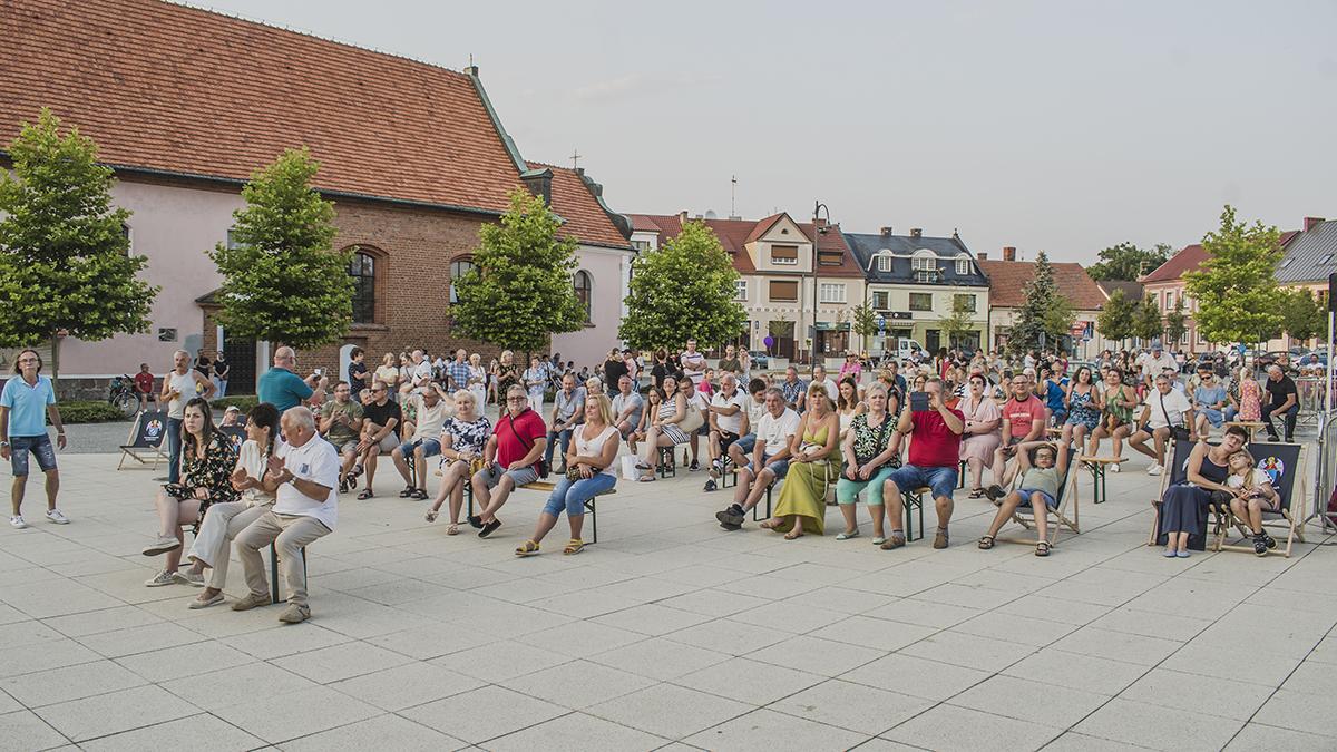 Publiczność siedzi na ławkach na placu