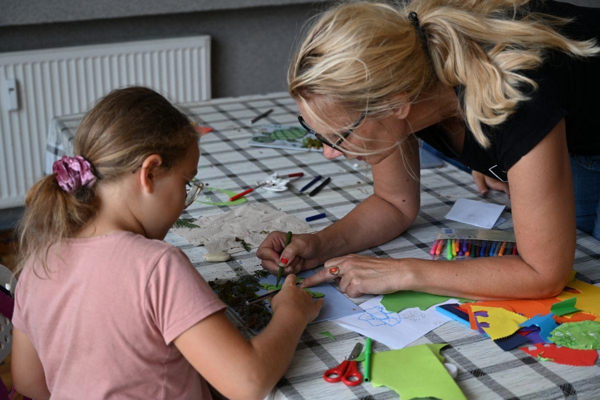 Kobieta pomaga dziewczynce malować pracę plastyczną