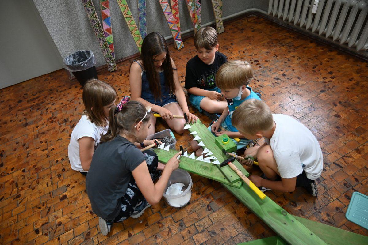Grupa dzieci na podłodze przy montażu zębów dinozaura