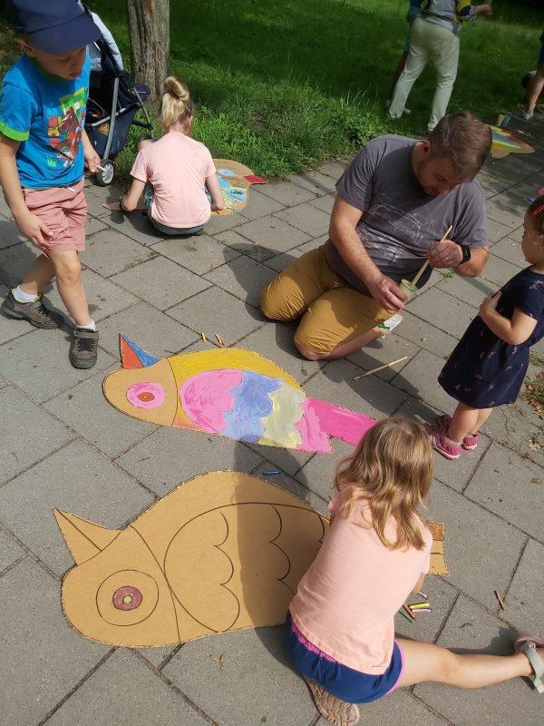 Grupa dzieci i dorosły mężczyzna malują sylwety wyciętych ptaków na chodniku