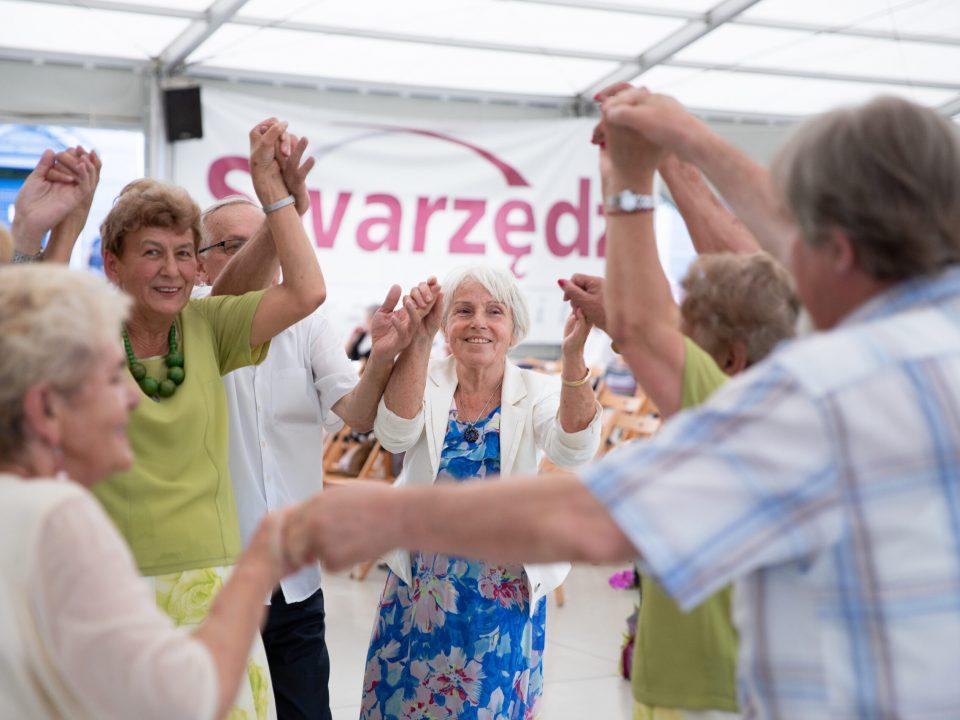 Grupa tańczących osób, w tle napis Swarzędz