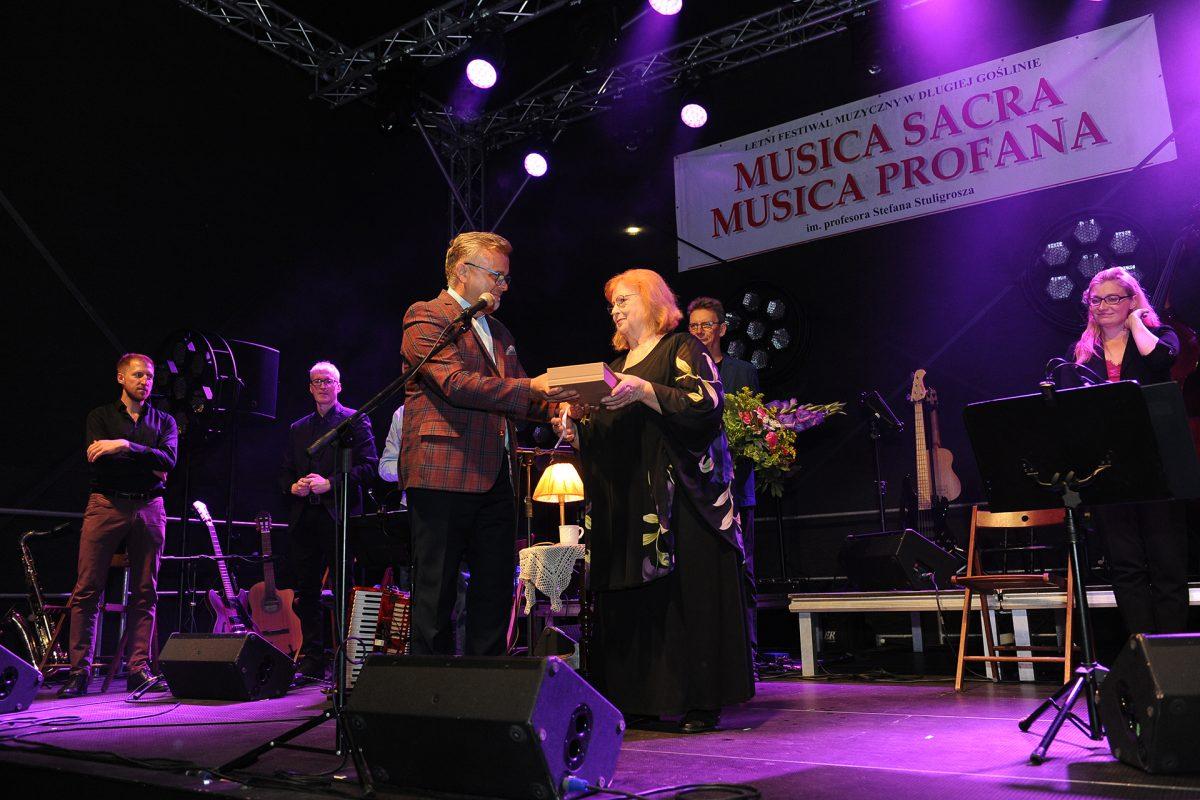 Ksiądz wręcza prezent Stanisławie Celińskiej na scenie